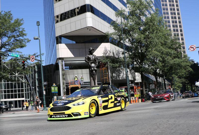 "Brad Keselowski, the 2013 Bank of America 500 winner, drives a NASCAR stock car through uptown Charlotte, North Carolina, during Charlotte Motor Speedway's ""Laps around Uptown"" parade on Tuesday."