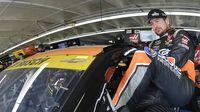 Kurt Busch climbs into his car before a practice run Friday at Charlotte Motor Speedway.
