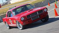 A vintage Mustang shows a little muscle on the AutoCross course during opening day of the 22nd annual Goodguys Southeastern Nationals at Charlotte Motor Speedway.